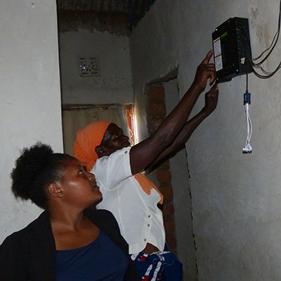Two women look at a battery/control box unit inside the home