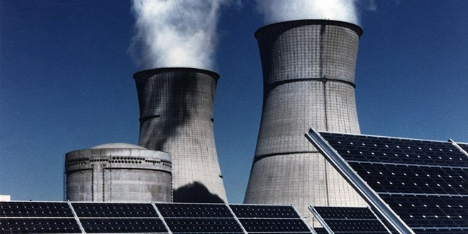 Stacks from a nuclear power plant are seen in the distance with solar panels in the forefront.